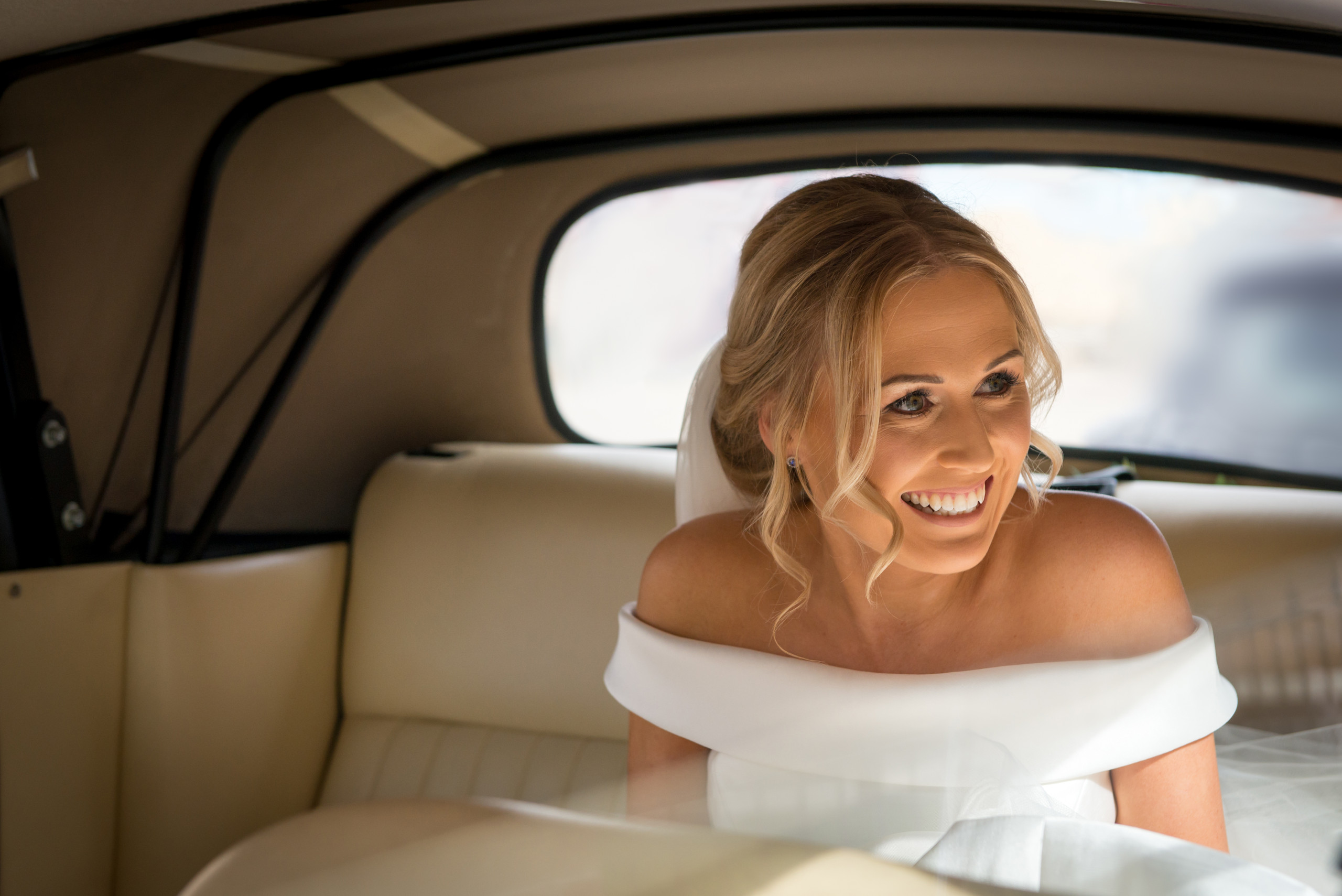 Relaxed bride smiling in vintage wedding car on morning of wedding on way to church