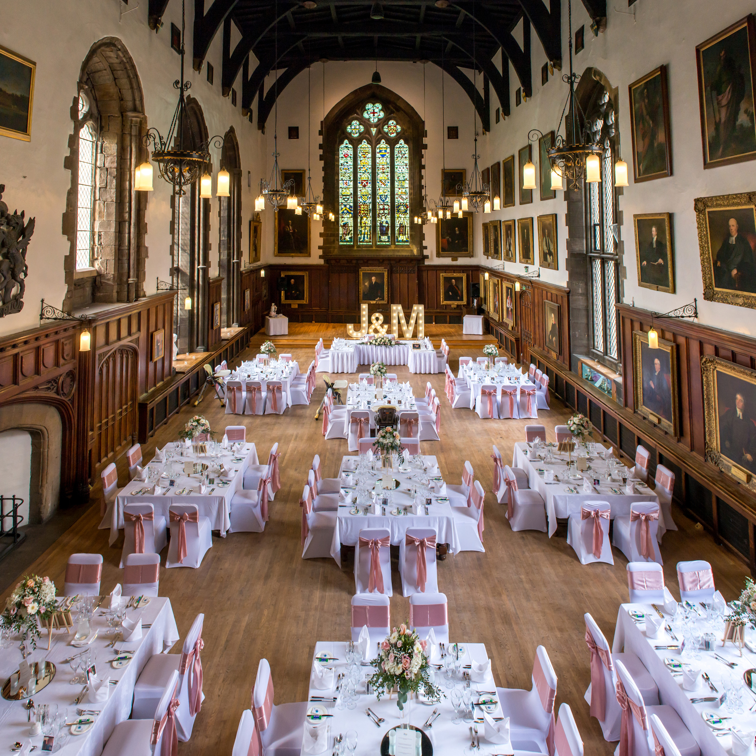 Photograph from balcony of wedding breakfast room decoration and seating arrangement and layout of Bishops Hall of historic venue Durham Castle in Durham City