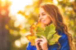 Cute smiley woman holding autumn leafs i