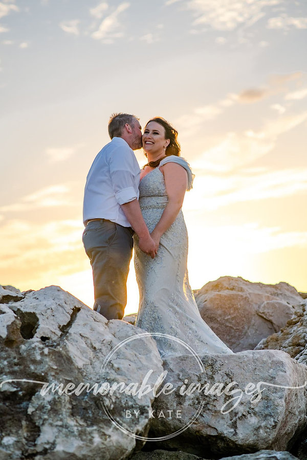 Bride and groom on rocks at St Petersburg Beach, Florida