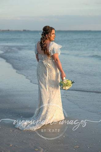 Bride on the beach, holding bouquet