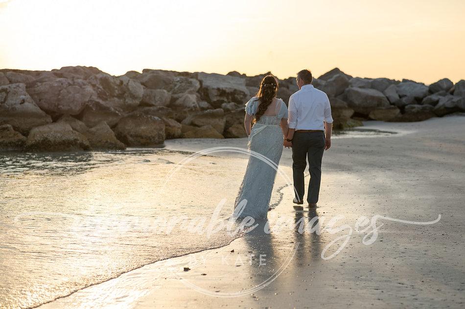 Bride and groom walking along St Petersburg Beach, Florida