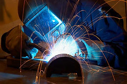 welder using welding torch on metal with sparks