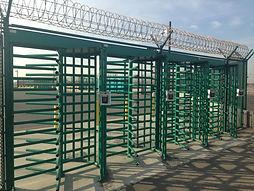 green turnstiles with razor ribbon on top