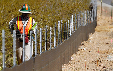 construction worker standing by farm with barbed wire