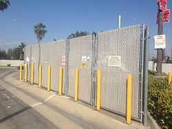 chain link fences with yellow posts near street