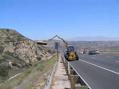 crane on california freeway performing construction on mountain side