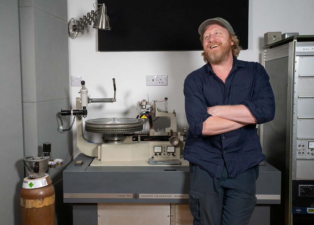 Photo of record producer Keith Tenniswood in front of one of the Neumann Cutting lathe's at Curve Pusher Studios