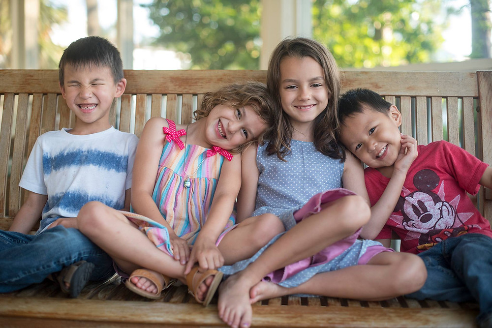 The kids laughing on a bench