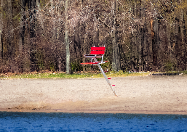 A lonely red lifeguard chair