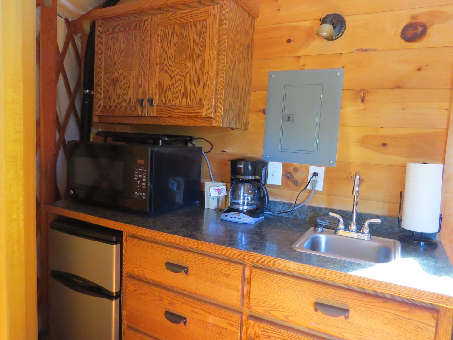 A small efficiency kitchen with a small fridge, microwave, coffee pot, sink, electric skillet, toaster, dishes, flatware and a gas grill are available in the Nantahala yurt.