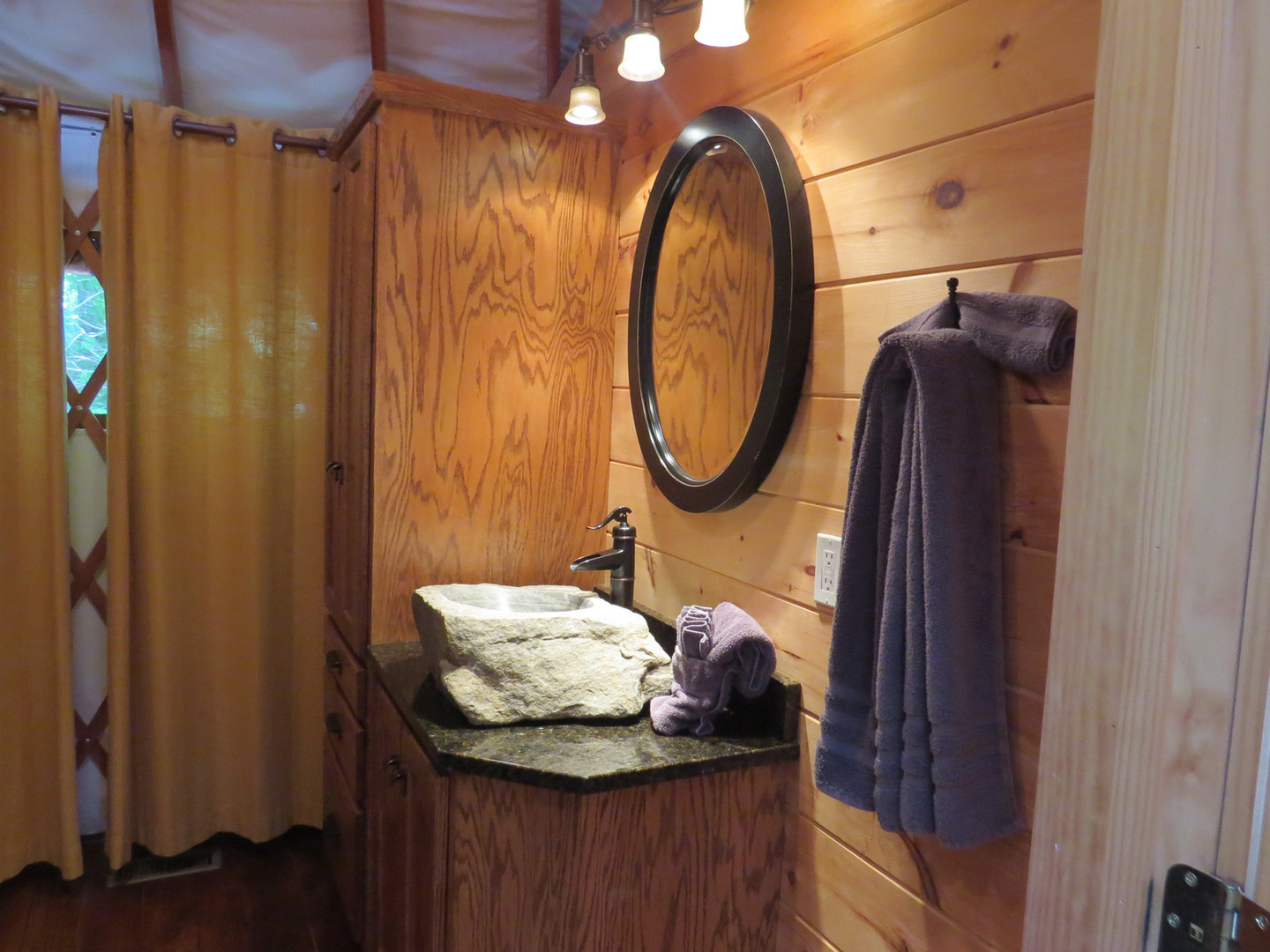 A lush private bath awaits guests in the Nantahala yurt, complete with handmade rock sink, walk-in shower, and all towels provided for your stay.