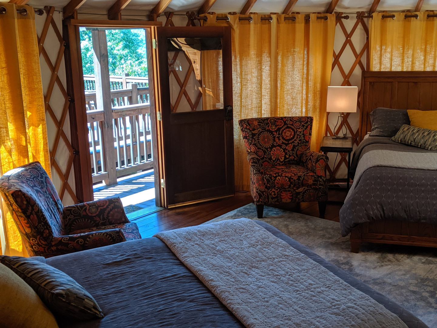 Two queen beds with lush Crate & Barrel linens await guests in the Tsali yurt.