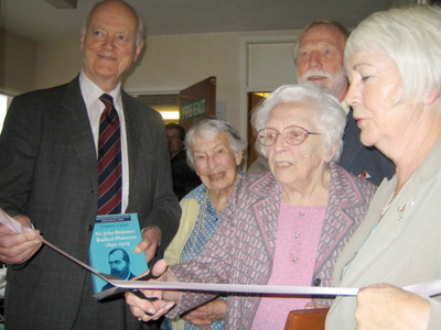 The ribbon is cut by Mrs Phyllis Latham, one of our more senior parishioners, with Sir Hugo Brunner (left), Ruth Cottle (grand-daughter of Ezra Gandy, the Architect of the original Parish Room), and Bob Heaton and Veronica Oliver of ABCA. The book being held by Sir Hugo is a biography of Sir John Brunner by Stephen Koss (photo by Rosemary Mullett)