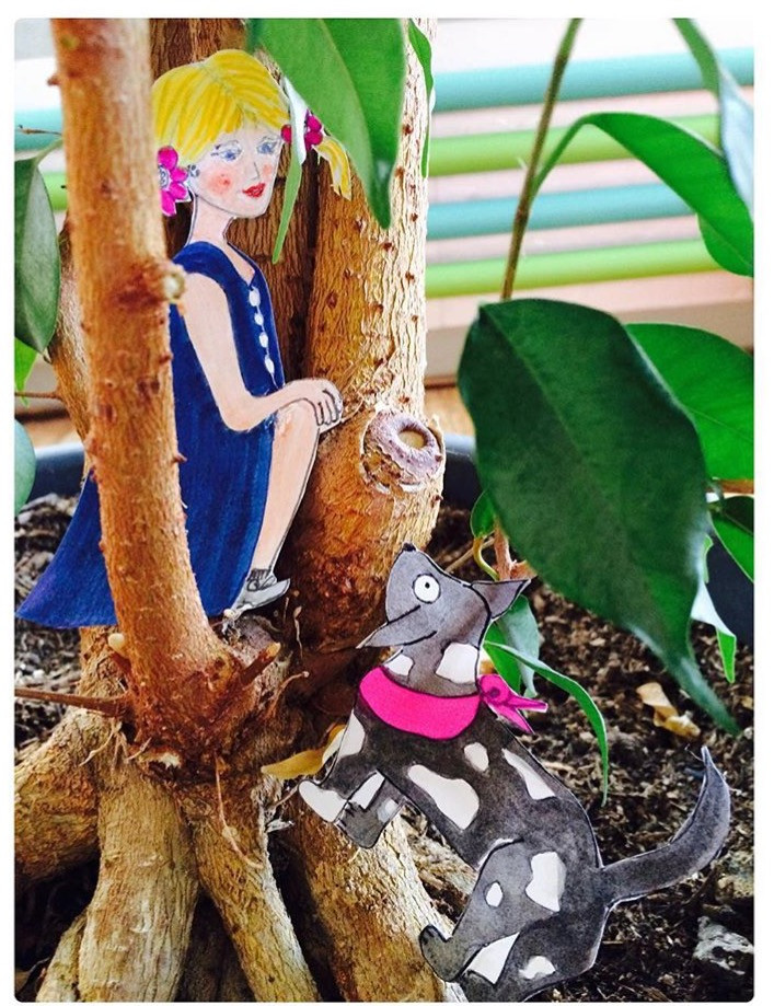 Frau (Papierzeichung ausgeschnitten)  sitzt zufrieden zwischen einem Pflanzenbaum. Zu ihren Füssen steht ein Hund.