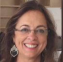 Foto de mulher usando óculos de grau e sorrindo.