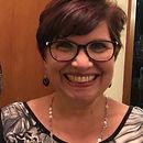 Foto de mulher, usando óculos de grau e sorrindo.