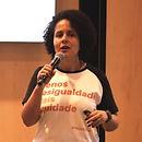 Foto de mulher falando ao microfone e vestindo camiseta com os dizeres: menos desigualdade, mais equidade.