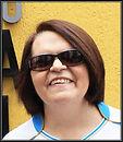 Foto de mulher usando óculos escuros, cabelos curtos e sorrindo.