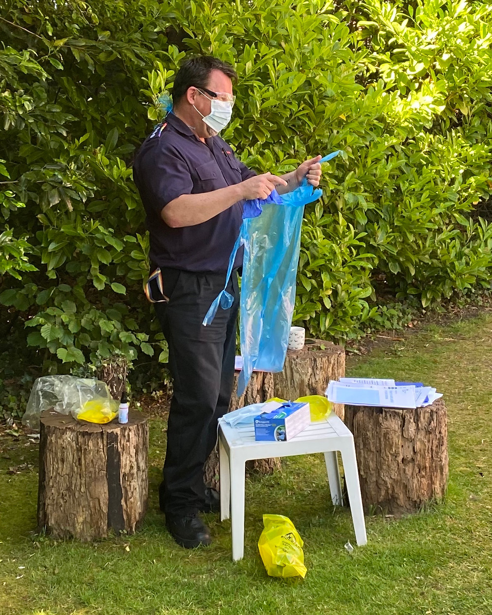 Volunteer Mick Pitney shown demonstrating personal protective equipment, mask and plastic apron