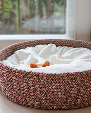 An empty dog bed basket with only dog bo