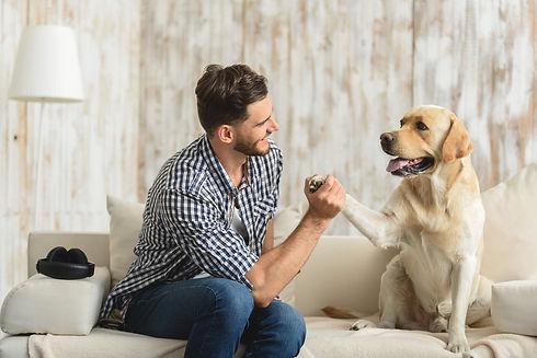guy on the sofa holding paw of dog.jpg