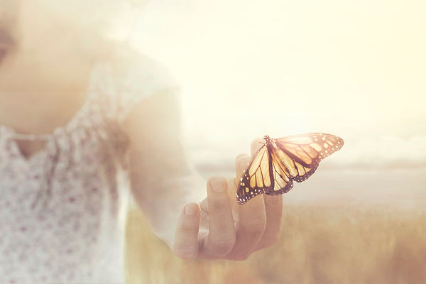 a butterfly leans on a hand of a girl in