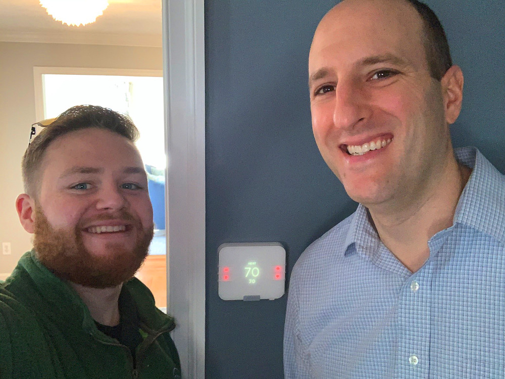 A home energy specialist with customer and the REAX smart thermostat