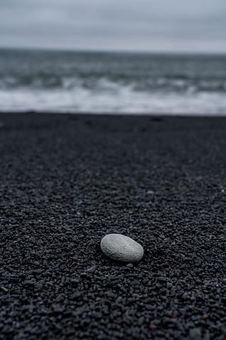 White pebble on black sand