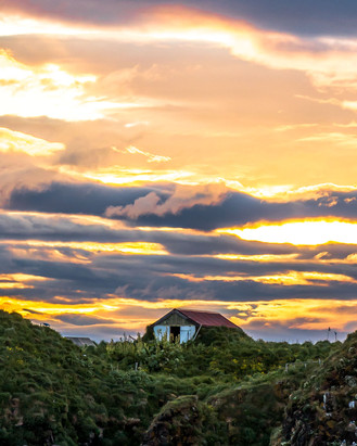 Farmhouse on the cliff at sunset