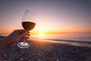 Person holding glass of red wine during