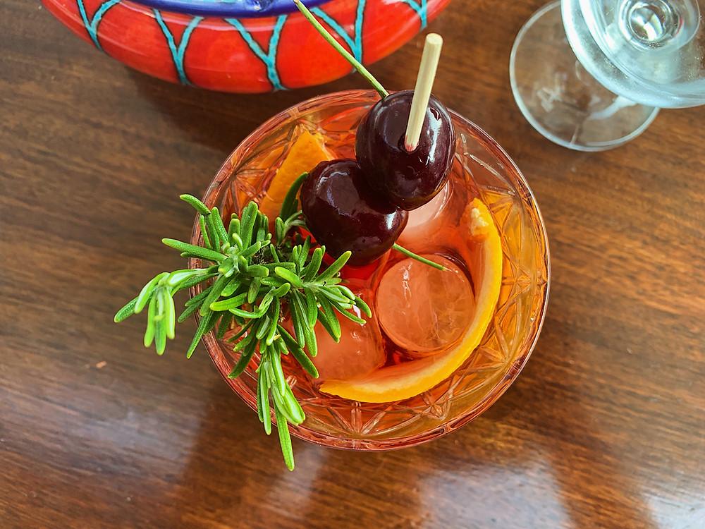 Negroni made with campari, gin, and vermouth.  Garnished with Rosemary Shrub, Orange Twist, and Amarena Cherry