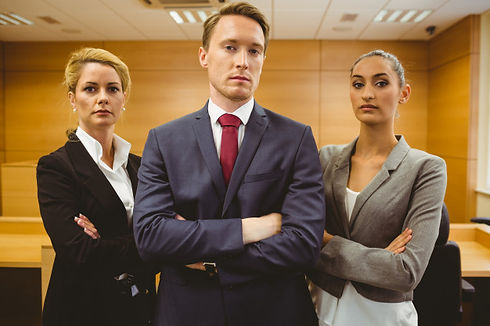 tres-abogados-serios-pie-brazos-cruzados
