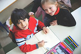 Two children, sitting at a table with color pencils and paper, smile and look up.
