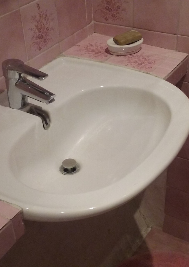Salle d'eau rose & coin lavabo avant home staging