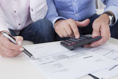 two people using a calculator an looking at invoices