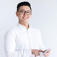 smiling-asian-man-using-tablet-computer_