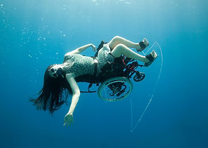 Woman dancing  in wheelchair under water