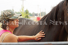 Roanna Irvine brushes Jenny, the black mare, with her hand during a break. (Lailani Upham photo)