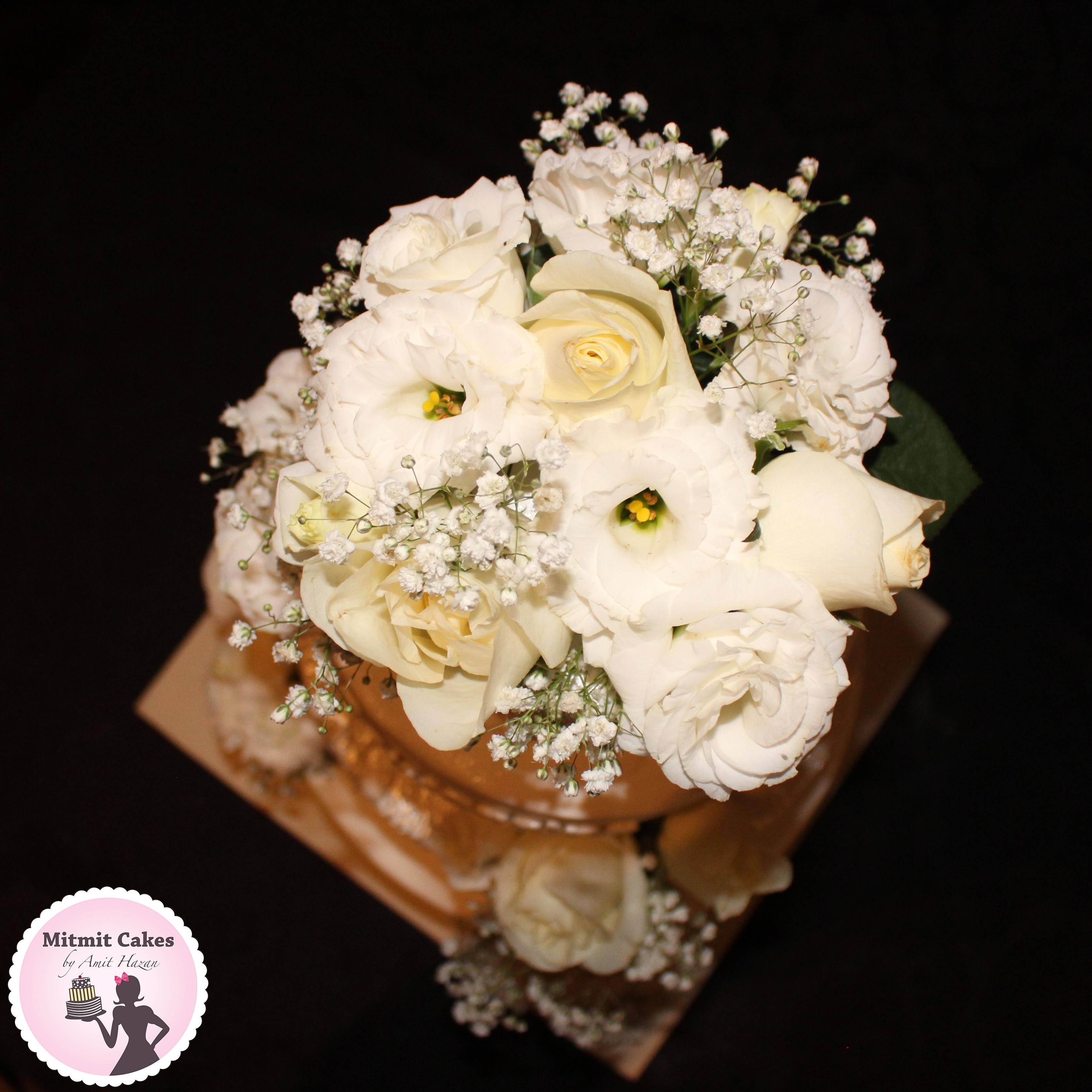מבט עליון על עוגת חתונה עם זר פרחים