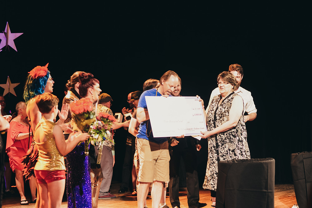 A picture of a large check being presented to Mic Drop winner Jason Keezer at the end of the show on the Liberty Hall Stage.