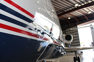 A glossy paint coat on a private jetliner. The jetliner is painted with red and blue strips from the side.