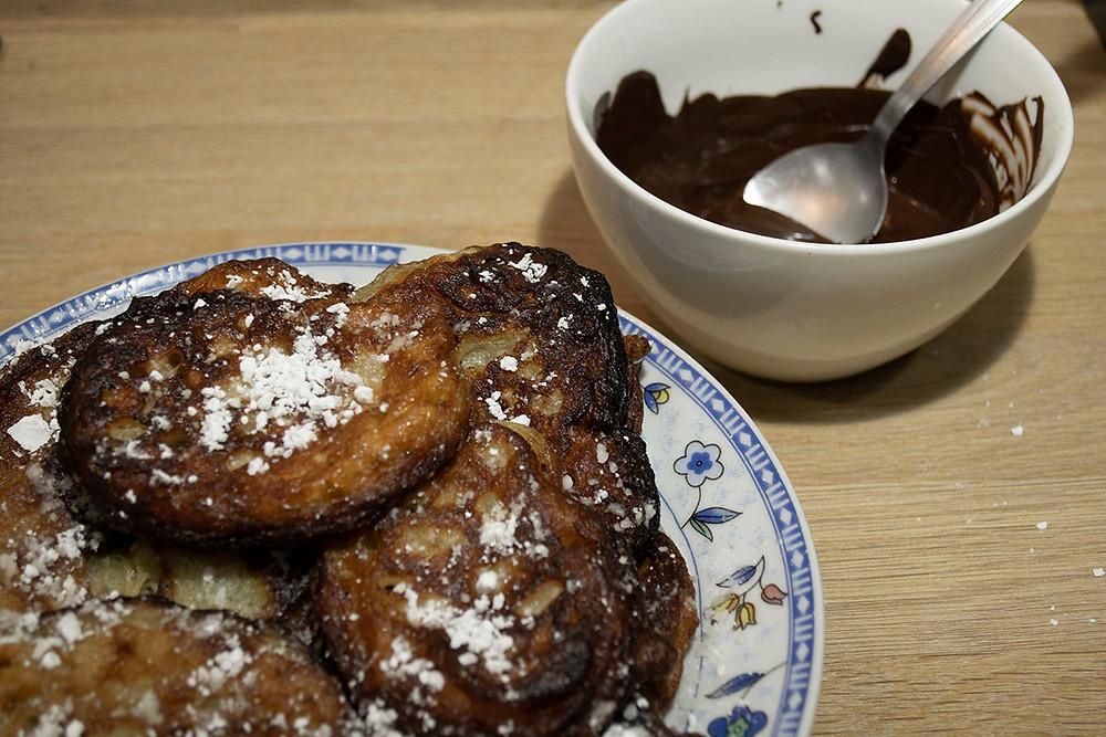 Beignets de banane et bol de sauce chocolat noir