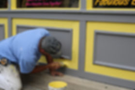 Painting the exterior of a HoA with yellow paint.