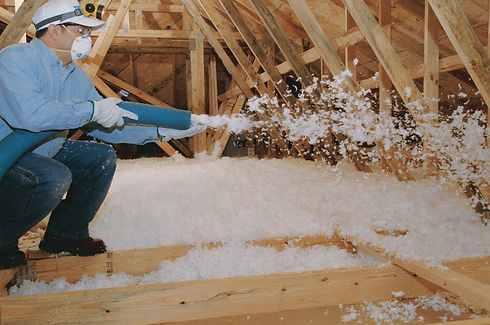 man wearing a mask while doing attic insulation