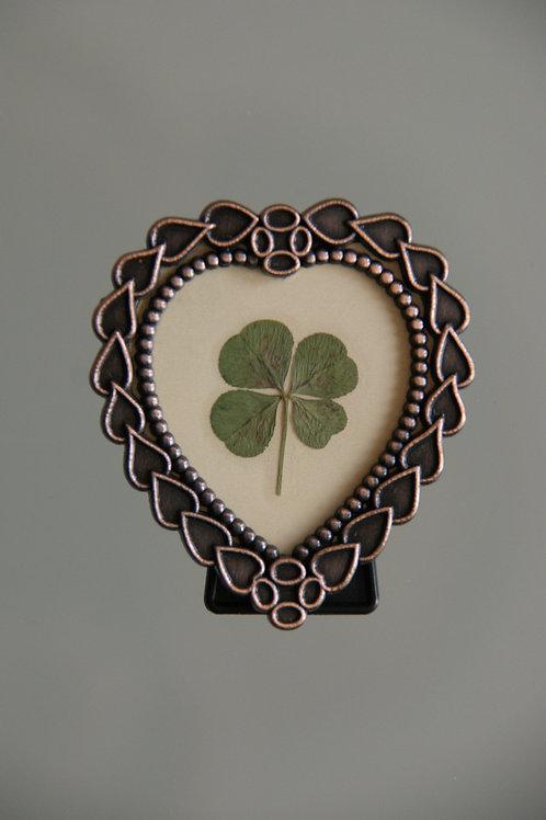 Four-leaf clover in heart-shaped frame