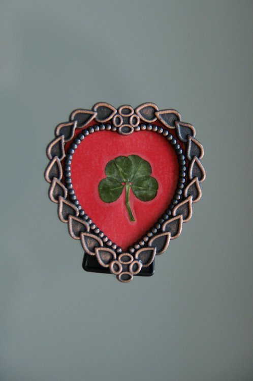 Four-leaf clover in heart-shaped frame