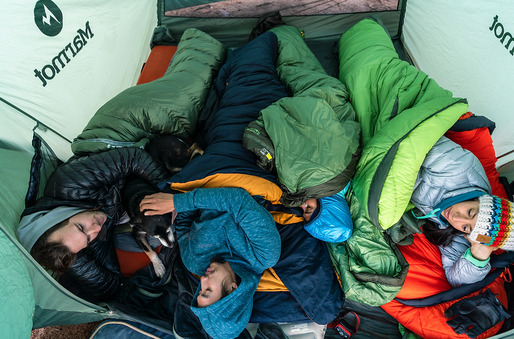 four people in sleeping bags inside tent