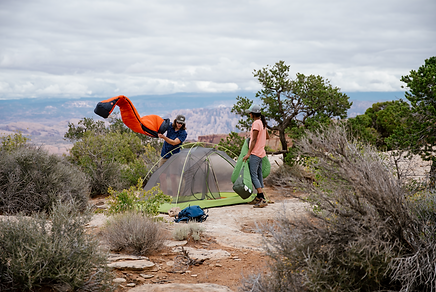 two people setting up a tent in the desert