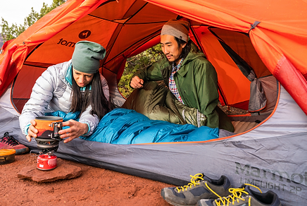 two people in a tent making coffee